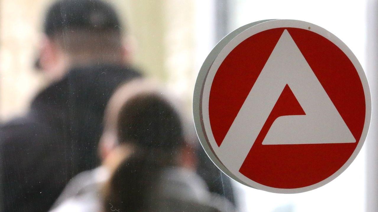 Arbeitslose sitzen in einem Zimmer beim Arbeitsamt, auf der Glasscheibe klebt das Logo der Arbeitsagentur