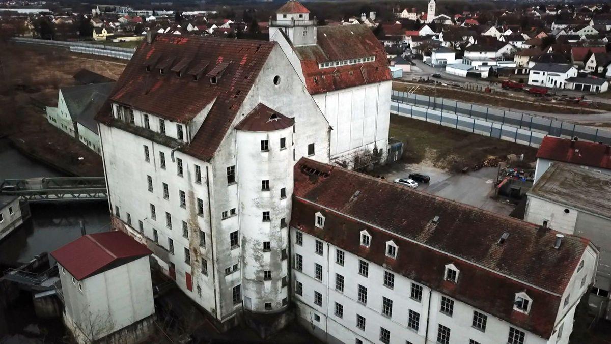 Ein weißes, vierstöckiges Gebäude mit rotem Ziegeldach und einem angebauten Halbturm, aus der Vogelperspektive betrachtet.