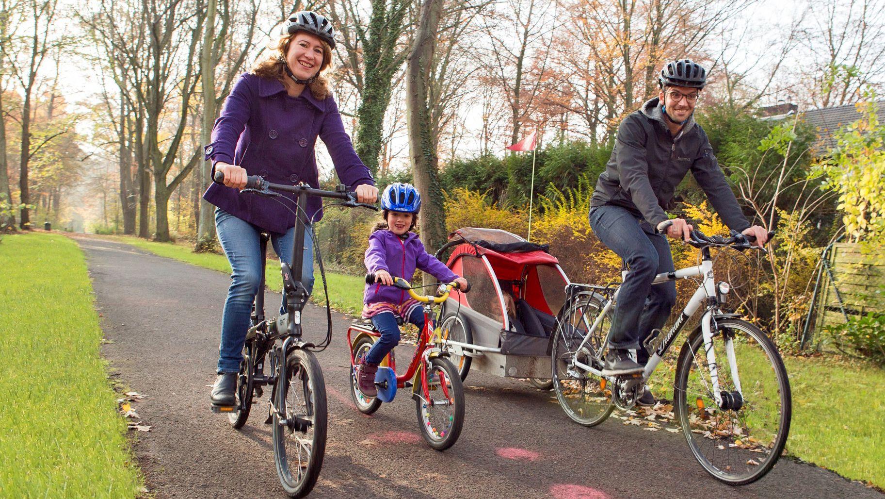 Familie mit Helmen fährt auf Fahrrädern