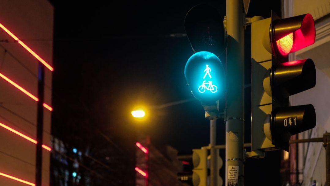 Eine grüne Fußgänger-Ampel bei Nacht.