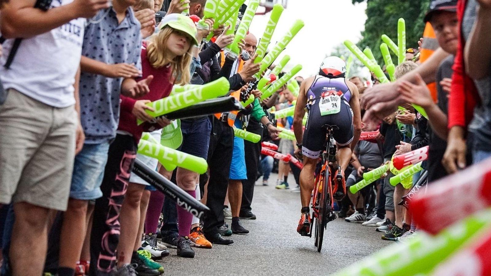 Triathlet wird auf dem Rad beim Triathlon in Roth angefeuert.