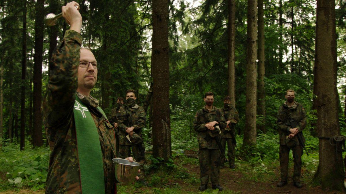 Militärseelsorger Jörg Plümper beim Feldgottesdienst. Uniformierte Männer und Frauen stehen im Kreis zwischen Bäumen im Wald.
