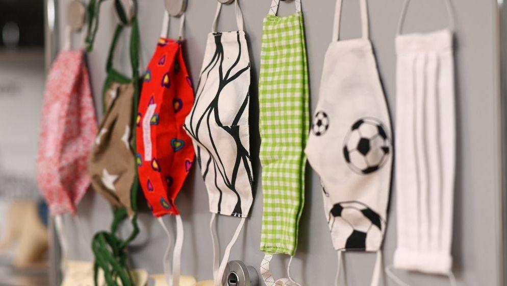 Verschiedene Mund-Nasen-Bedeckungen hängen an einer Wand.