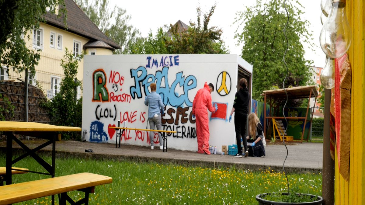 Jugendliche besprühen eine Garagenwand am Jugendzentrum Mühldorf mit Graffitis.