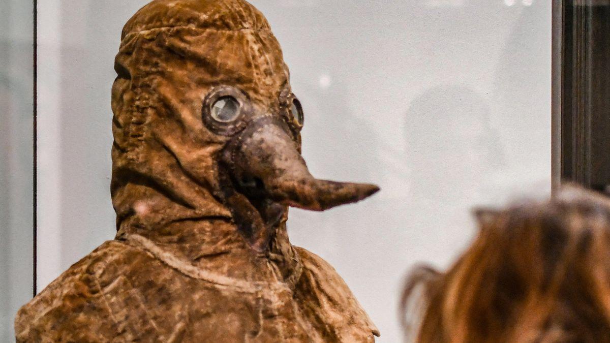Eine Besucherin betrachtet eine mittelalterliche Pestmaske in einem Museum in Berlin.