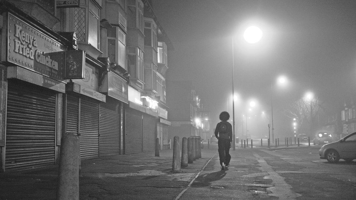 Ein Mann auf einer nebeligen Straße. Der Betrachter sieht seinen Rücken und seinen Afro.