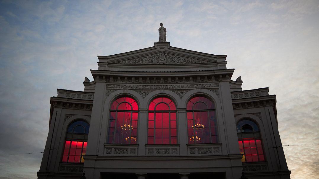 Fassade des Münchner Theaters rot erleuchtet