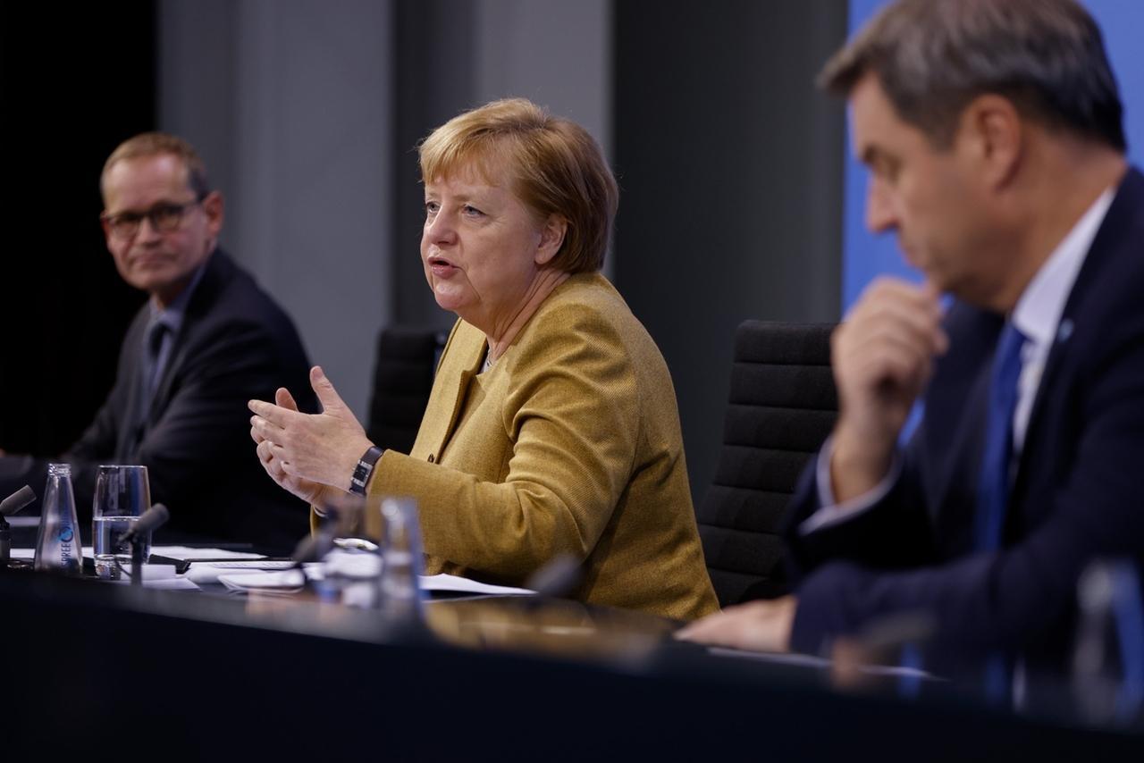 25.11.2020, Berlin: Bundeskanzlerin Angela Merkel (CDU) spricht im Bundeskanzleramt in der Pressekonferenz neben Bayerns Ministerpräsident Markus Söder (CSU - r) und BerlinsRegierendem Bürgermeister Michael Müller (SPD) . Sie hatten zuvor im Kanzleramt per Videokonferenz mit den Ministerpräsidenten der Bundesländer über die Verlängerung der Coronavirus-Restriktionen verhandelt. Foto: Odd Andersen/AFP/POOL/dpa +++ dpa-Bildfunk +++