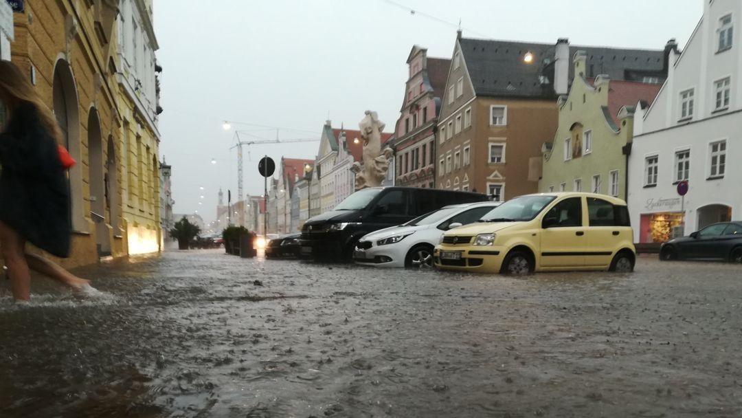 Eine Frau geht barfuß durch das Wasser in der Innenstadt in ein Haus. Außergewöhnliche Regenmassen hatten die Altstadt am 29.6. unter Wasser gesetzt.