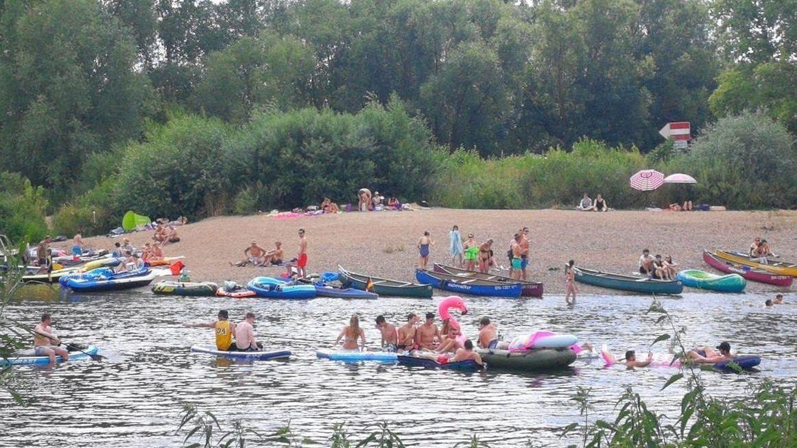 Menschen in Schlauchbooten und Luftmatratzen auf dem Altmain bei Volkach