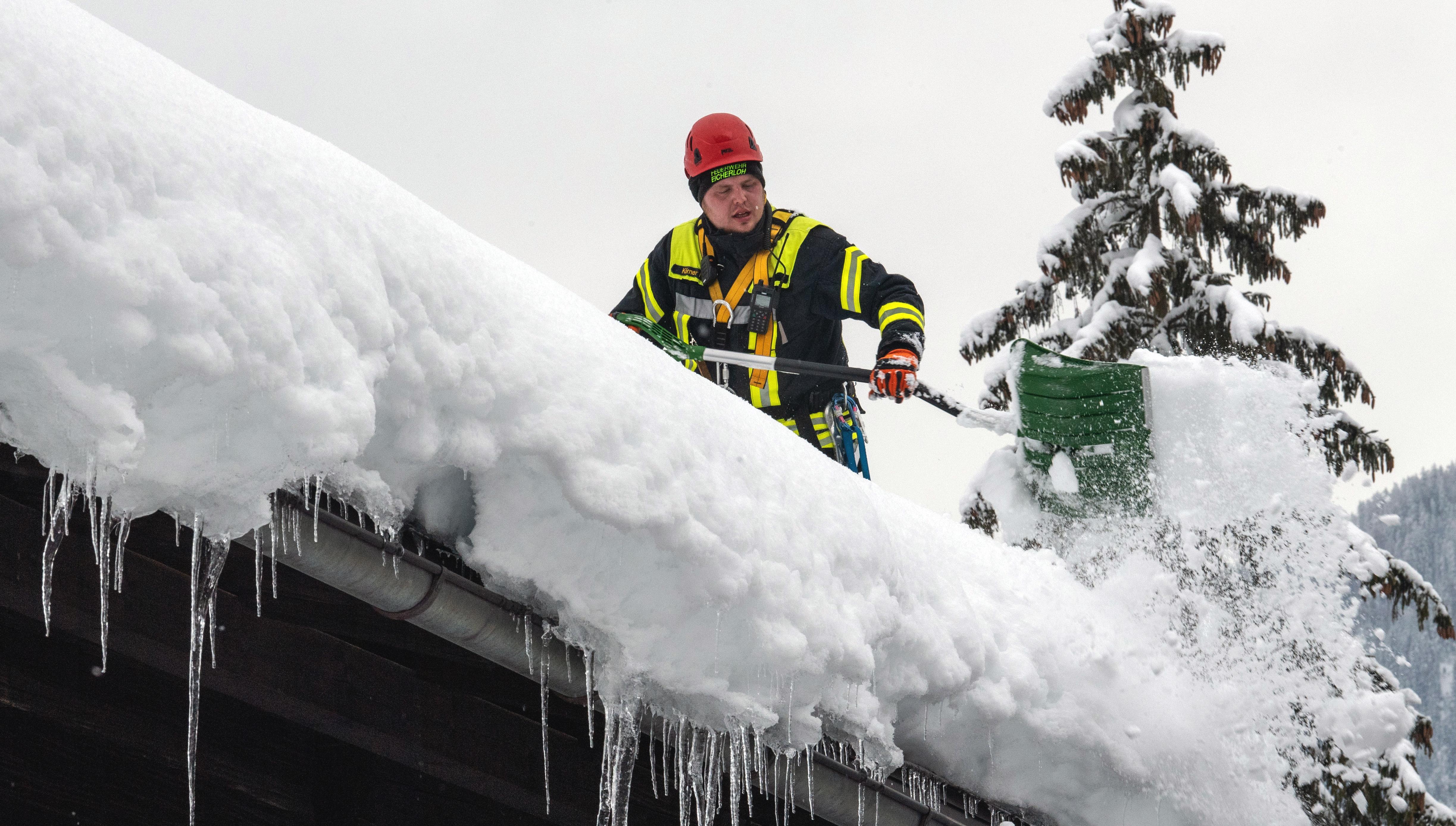 Ein Feuerwehrmann räumt Schnee von einem Dach