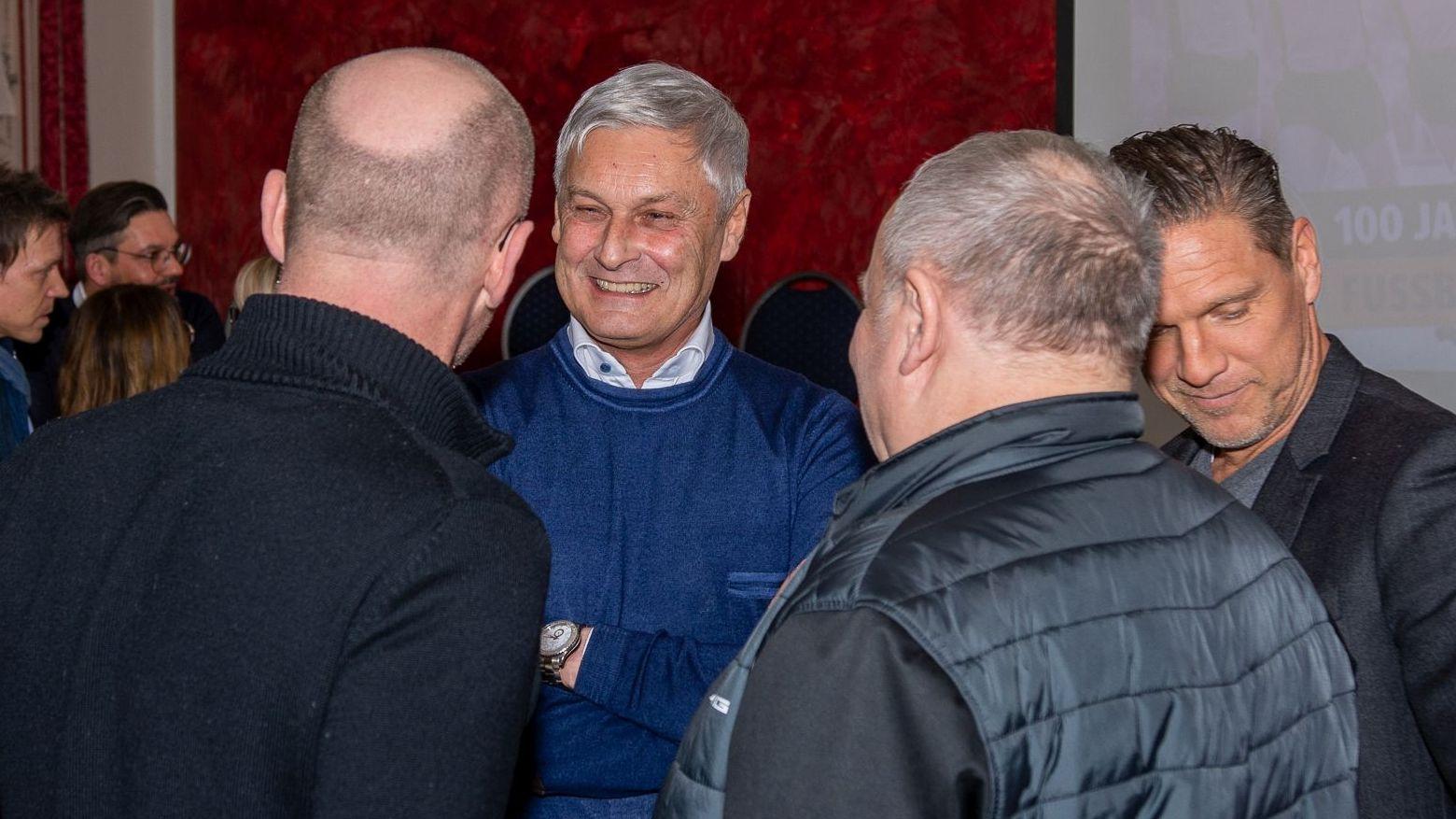 Vier Männer stehen beisammen, reden und lachen.