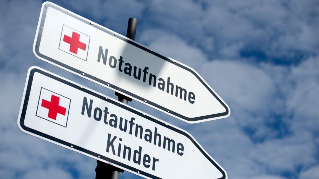 """Zwei Schilder mit der Aufschrift """"Notaufnahme"""" und """"Notaufnahme Kinder"""" stehen vor einem Krankenhaus."""