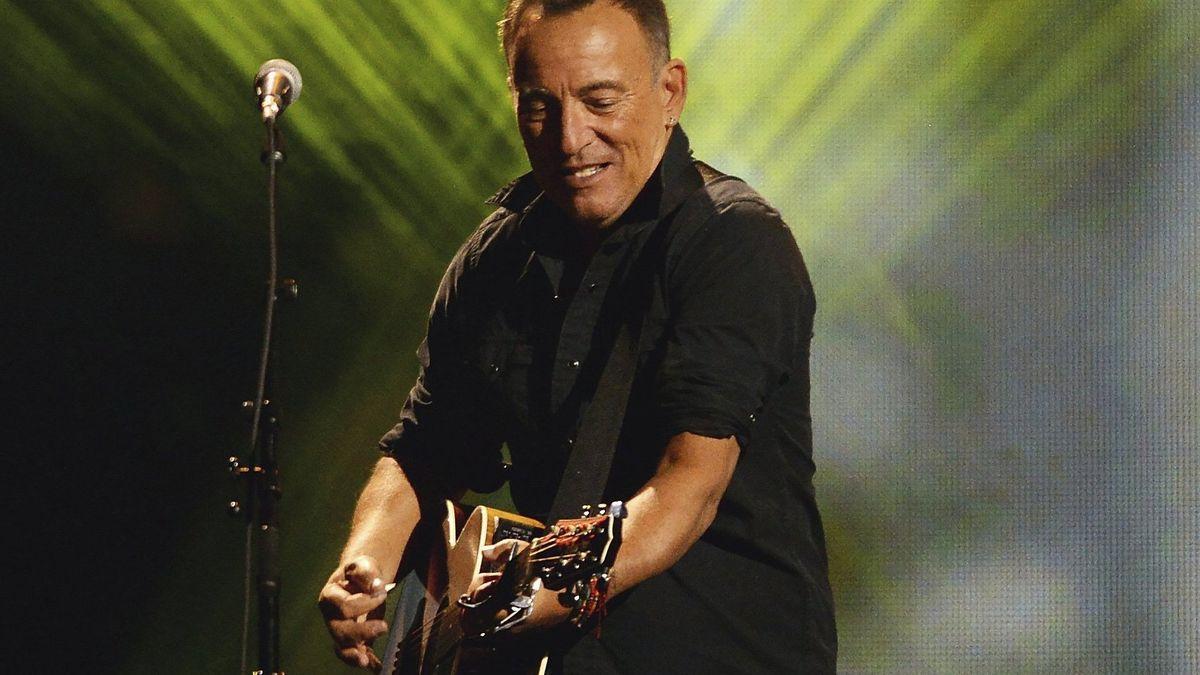 Musiker mit Gitarre spielt vor gelb-grünem Lichteffekt: Bruce Springsteen