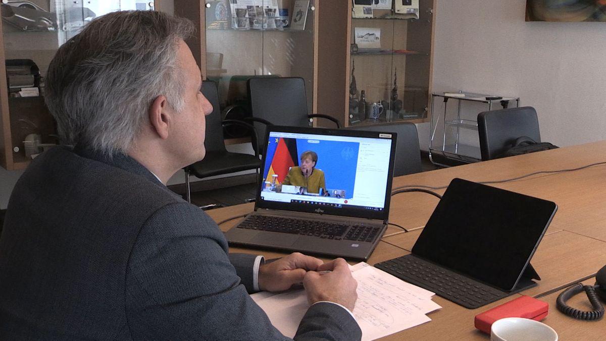 Ein Mann sitzt an einem Tisch, darauf ein Laptop mit erleuchtetem Bildschirm und ein Tablet-Computer mit schwarzem Bildschirm.