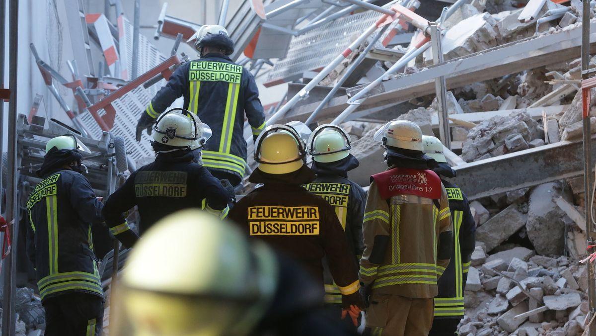 Düsseldorf: Feuerwehleute stehen in einer Hauseinfahrt vor Bauschutt.