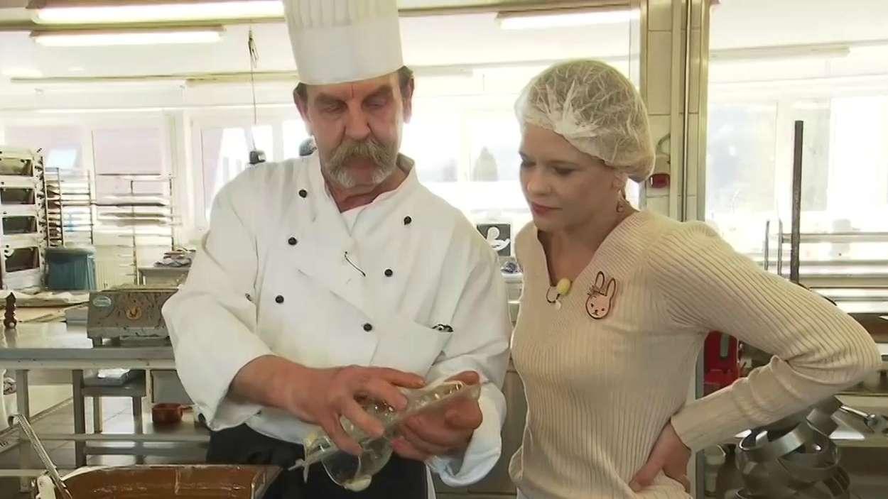 Ein Chocolatier der Schokoladenmanufaktur in Sandberg in der Rhön zeigt einer BR-Reporterin die Herstellung