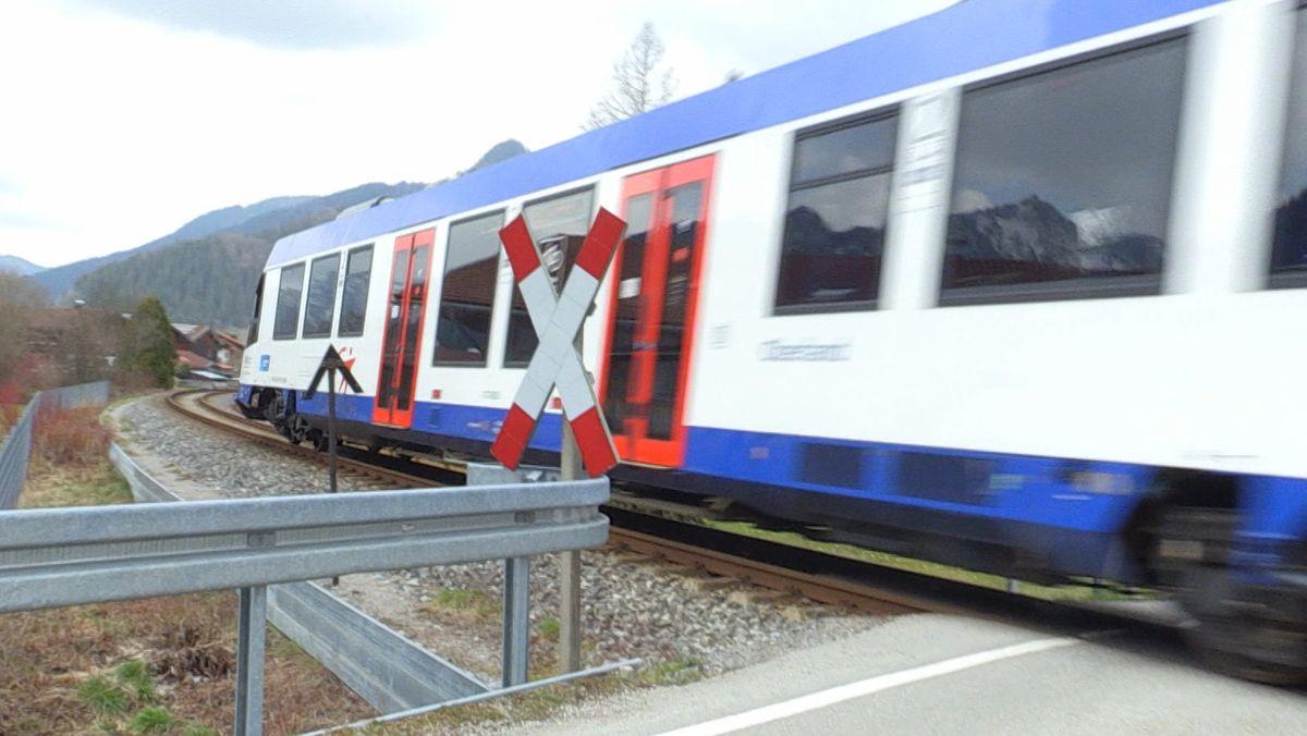 Ein Zug der Bayerischen Regiobahn, lackiert in weiß, rot und blau, fährt in einer Kurve über einen Bahnübergang. Im Vordergrund das weiß-rote Andreaskreuz als Hinweis auf den Bahnübergang.
