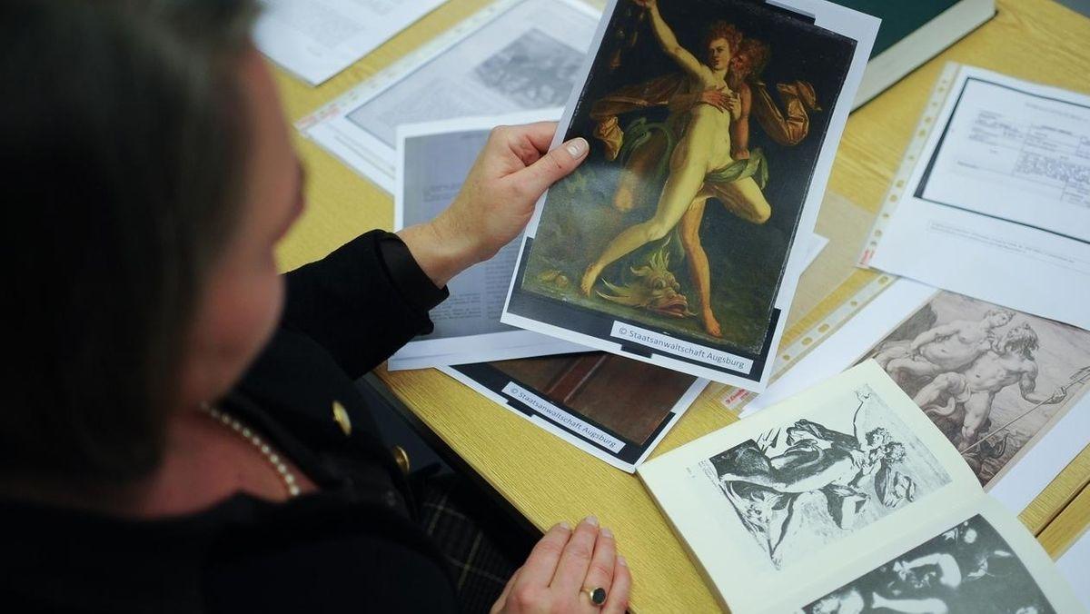 Eine Frau sitzt an einem Schreibtisch und vergleicht verschiedene Abbildungen eines Kunstwerks