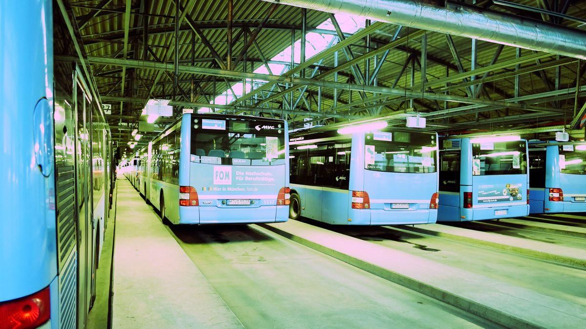 Busse in München stehen in einer Werkshalle.