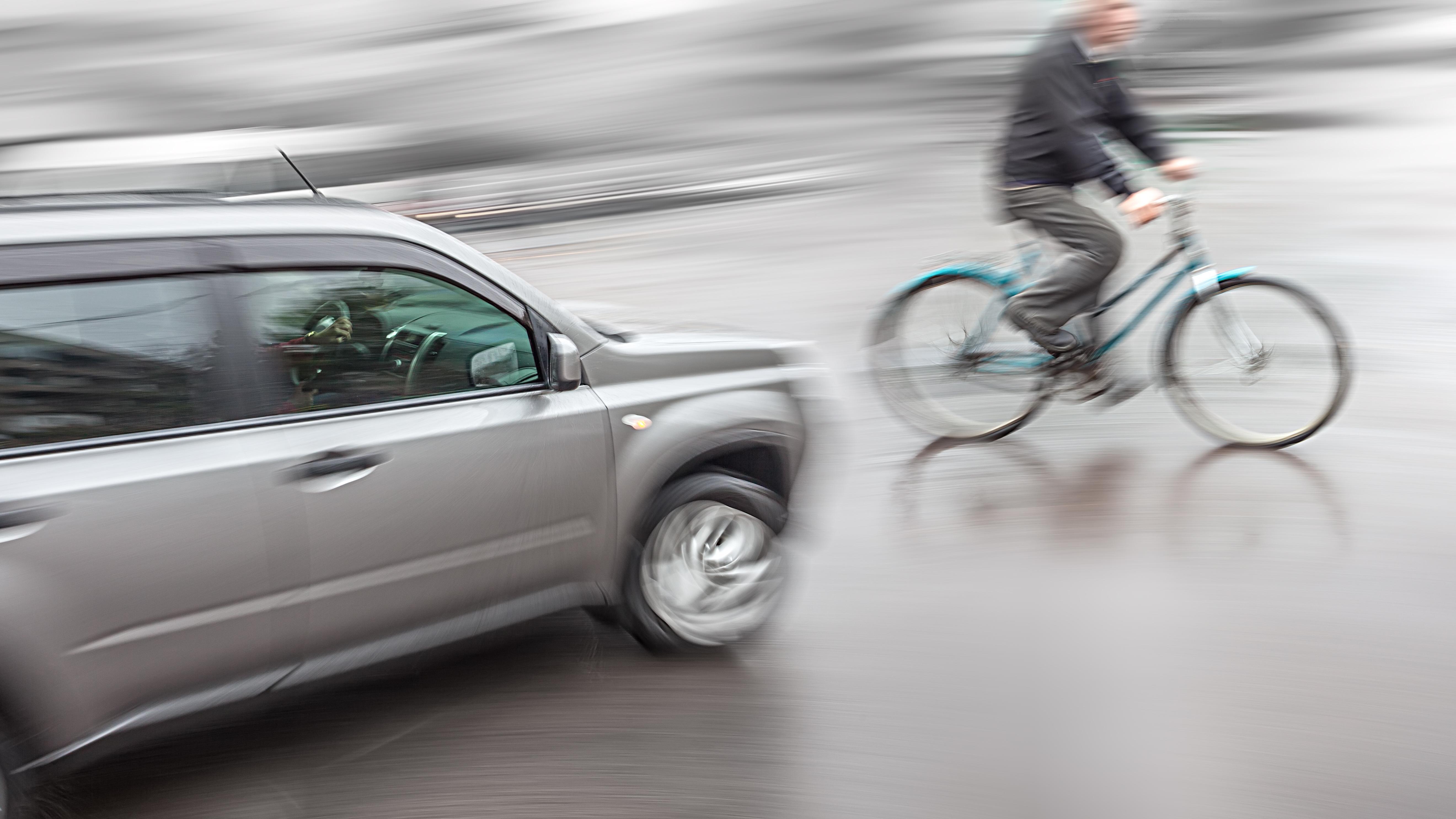 unscharf fotografiertes Auto, das auf einen Fahrradfahrer zufährt