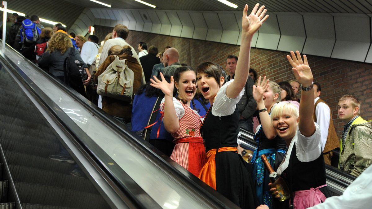 Besucherinnen fahren am ersten Oktoberfesttag in München die Rolltreppe der U-Bahnstation zur Theresienwiese empor.
