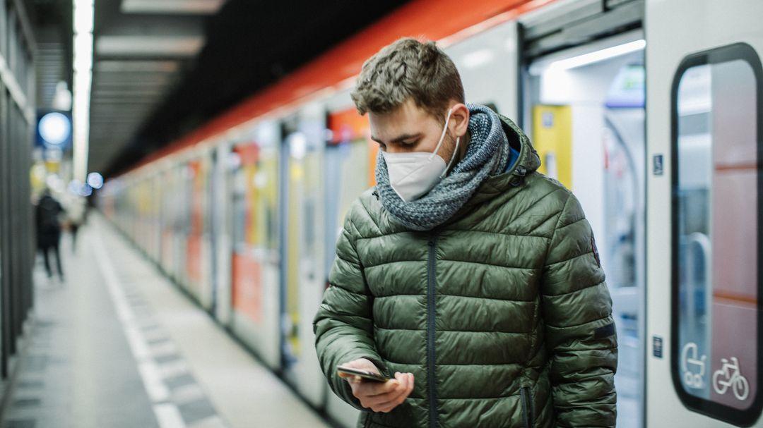 Ein Mann mit FFP2-Maske wartet am Bahnsteig auf die S-Bahn.
