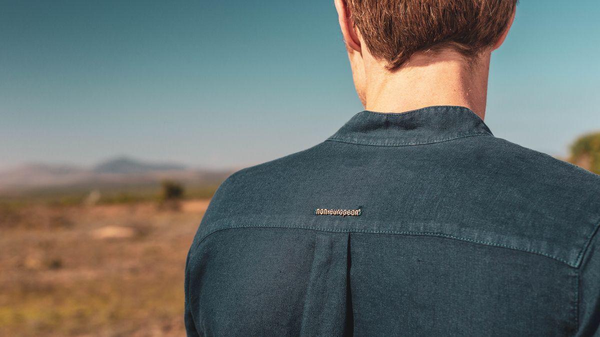 """Ein Mann mit dem Rücken zum Betrachter, auf seinem Hemd der Name des Labels: """"non-european""""."""