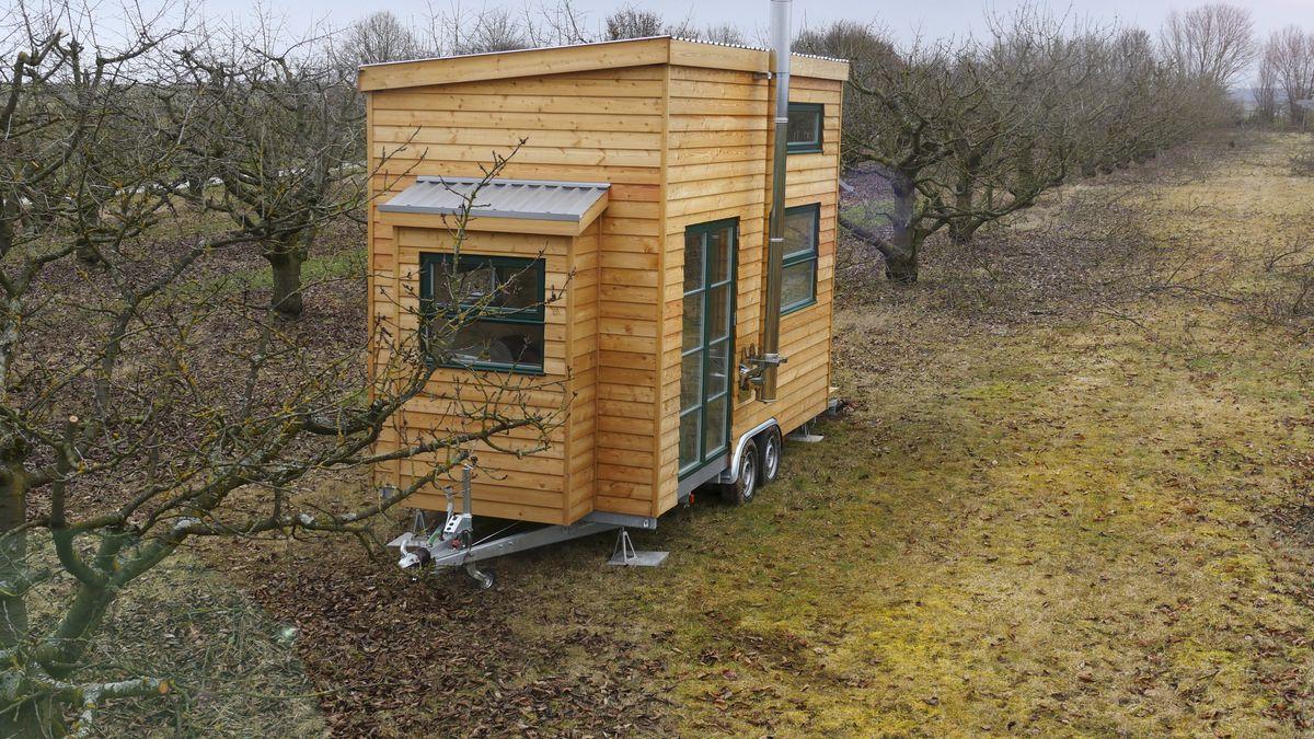 Ein kleines Holzhaus auf einem Anhänger steht auf einer Wiese.