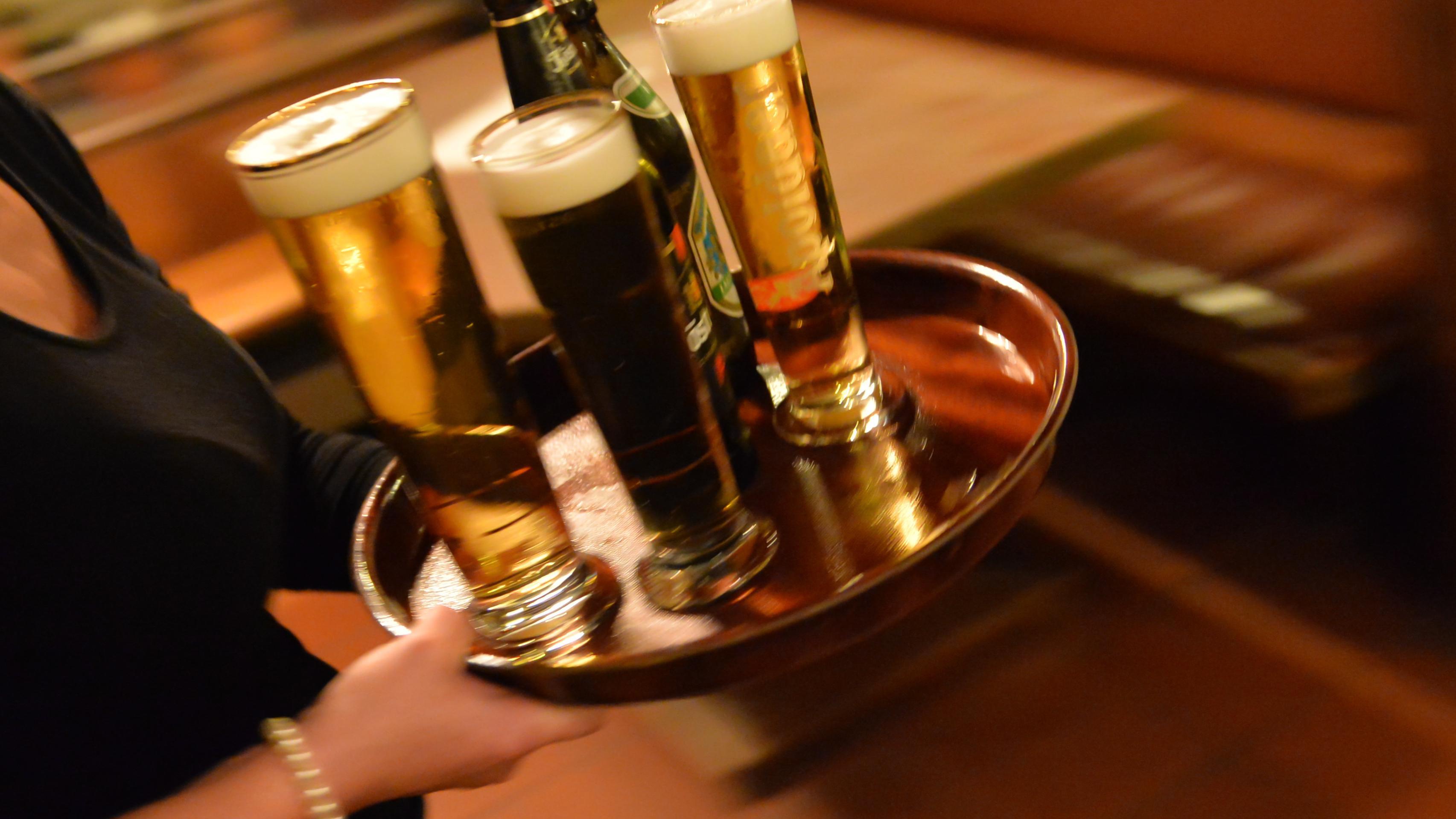 Bedienung trägt ein Tablett mit Bier