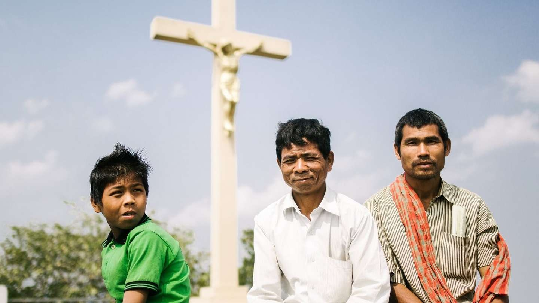 Katholiken in Indien: Zwei Männer und ein Junge sitzen vor einem Steinkreuz.