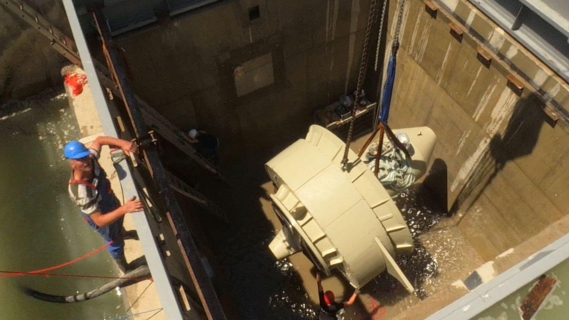 Arbeiter beim Einsetzen der ersten Turbine.