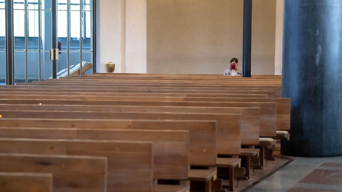 Eine Frau mit Mundschutz verfolgt einen Gottesdienst in der ansonsten fast menschenleeren St. Matthäuskirche in München.