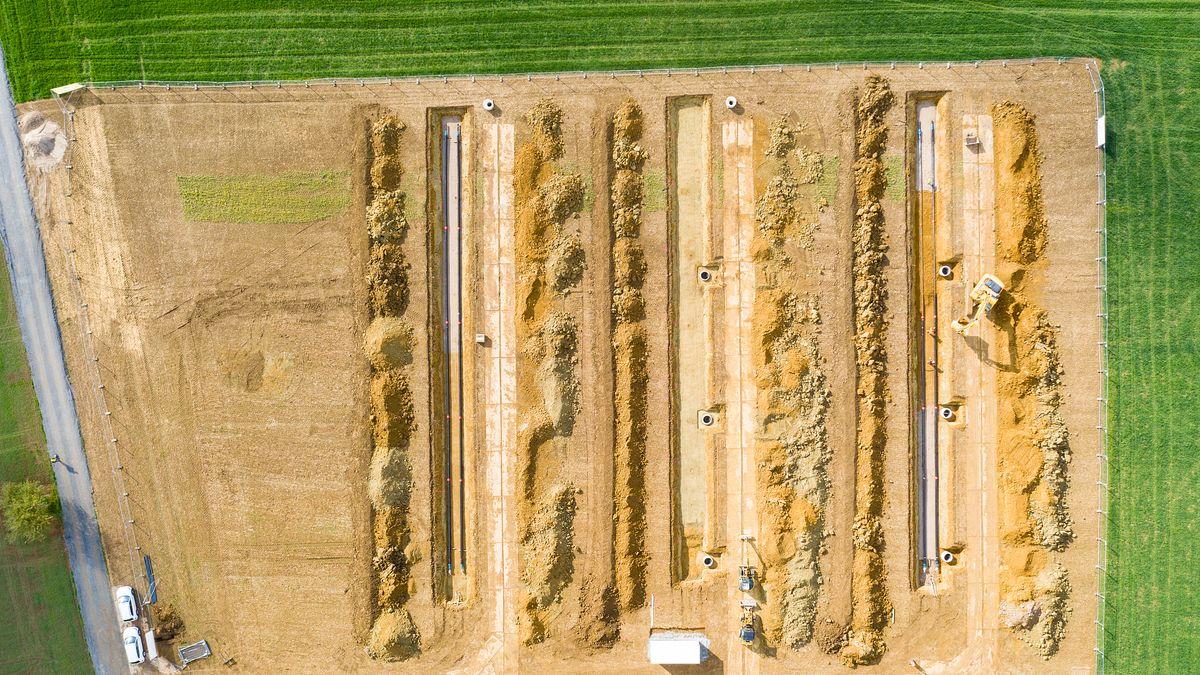 Drei Gräben in einer Wiese, in der Erdkabel verlegt werden.