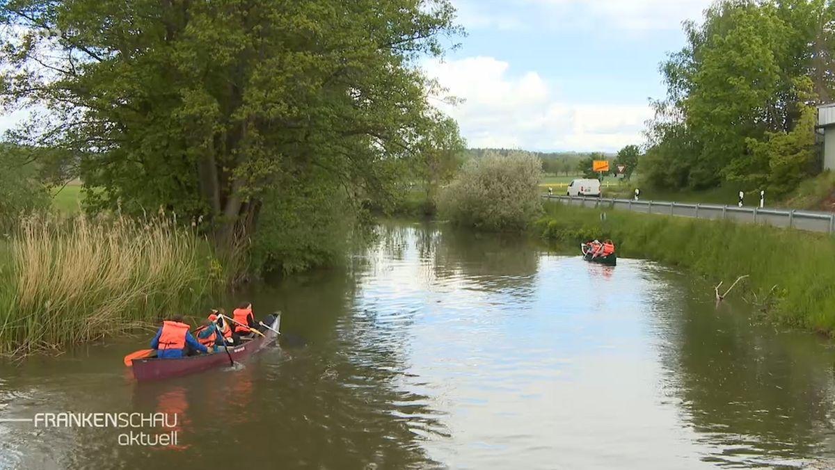 Mehrere Personen in Schwimmwesten sitzen in zwei Kanus und paddeln auf einem Fluss.