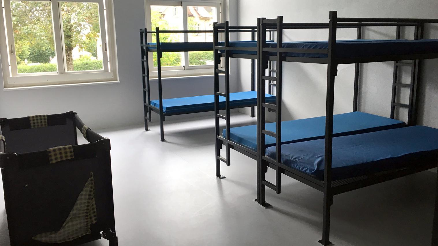 Stockbetten und ein Reisebett für Kleinkinder stehen in einem leeren Raum im Aslyzentrum Boudry in einem Workshop Nähen.