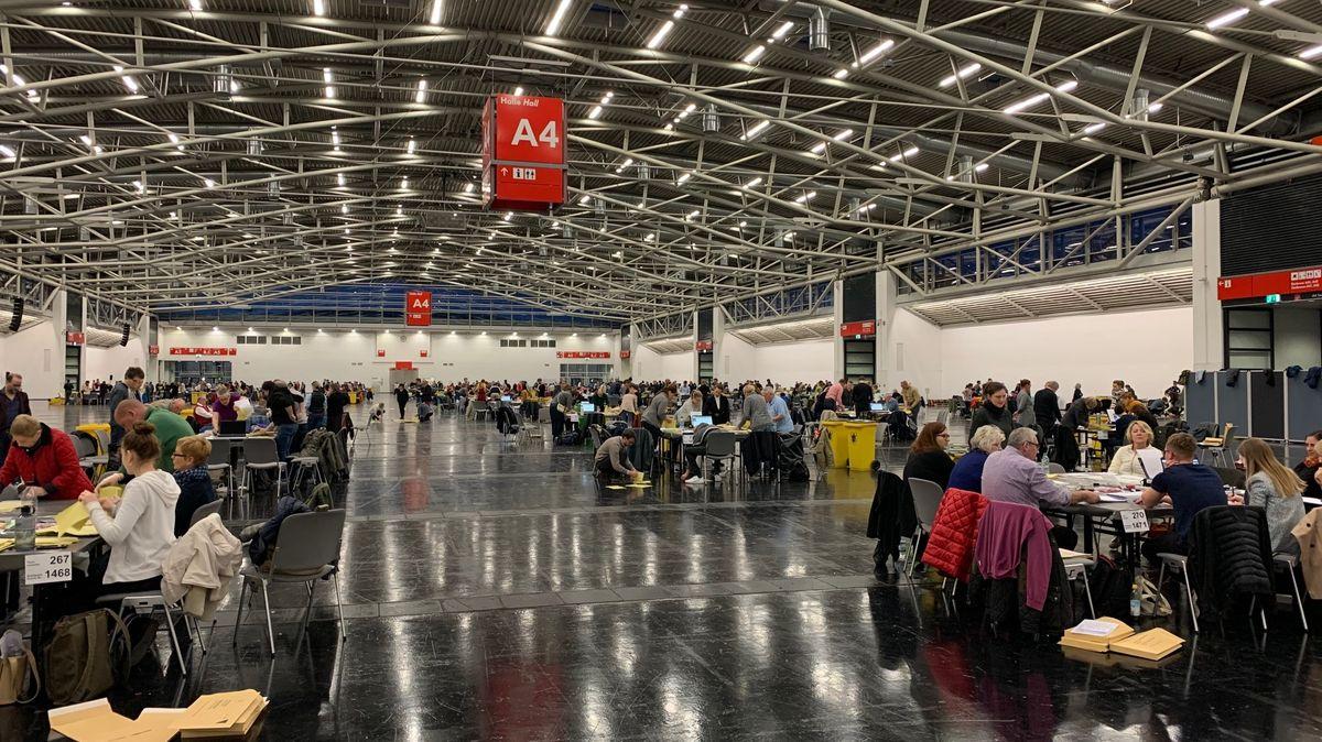 Blick in eine Halle der Messe München, wo die Wahlhelfer die Stimmzettel auszählen.