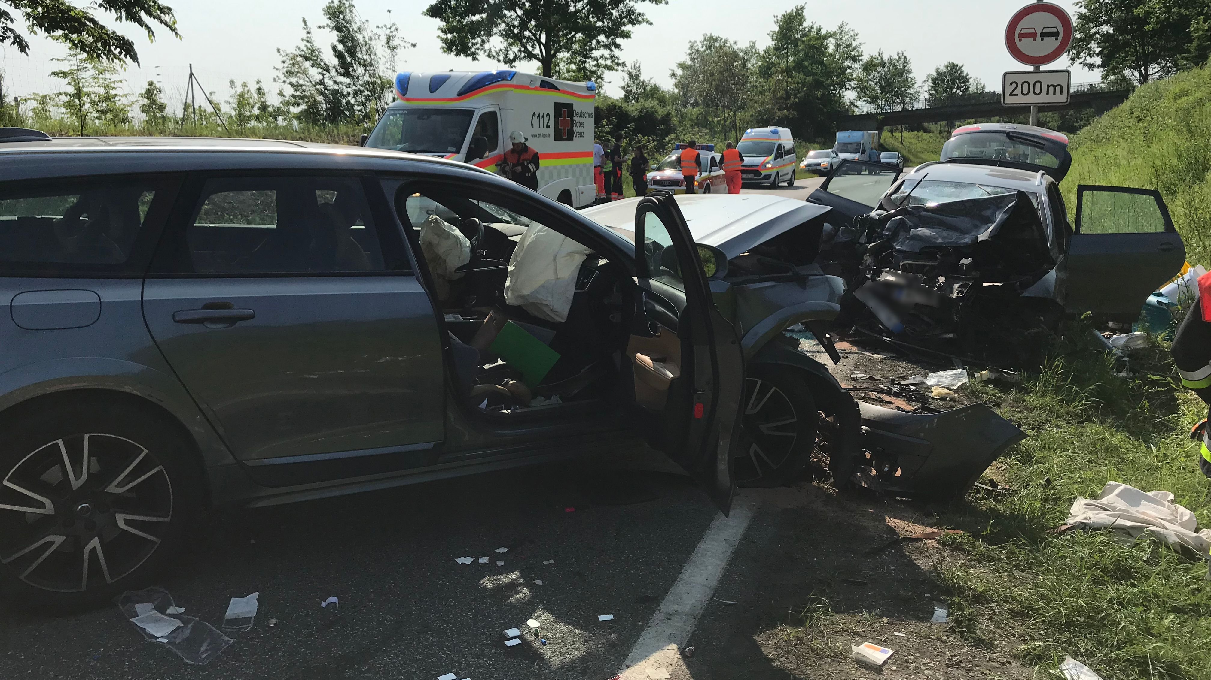 Zwei Unfallfahrzeuge auf der B31 bei Lindau - Rettungskräfte und Einsatzfahrzeuge im Hintergrund
