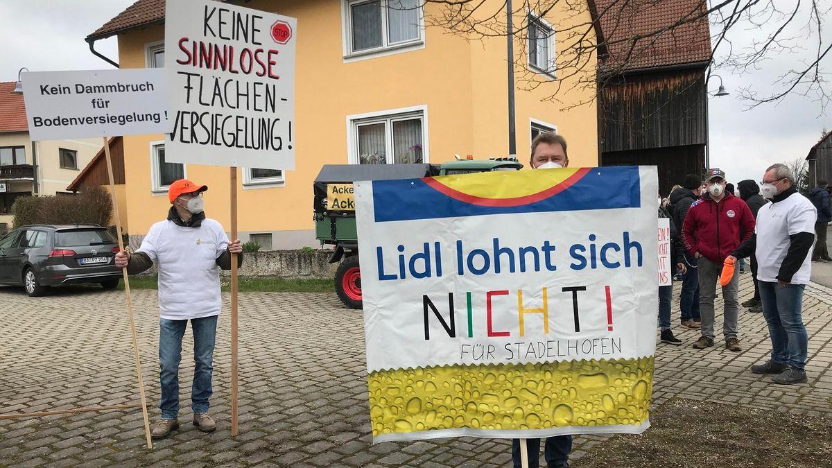 """Demonstranten halten Schilder hoch, eines trägt die Aufschrift """"Lidl lohnt sich nicht für Stadelhofen"""""""