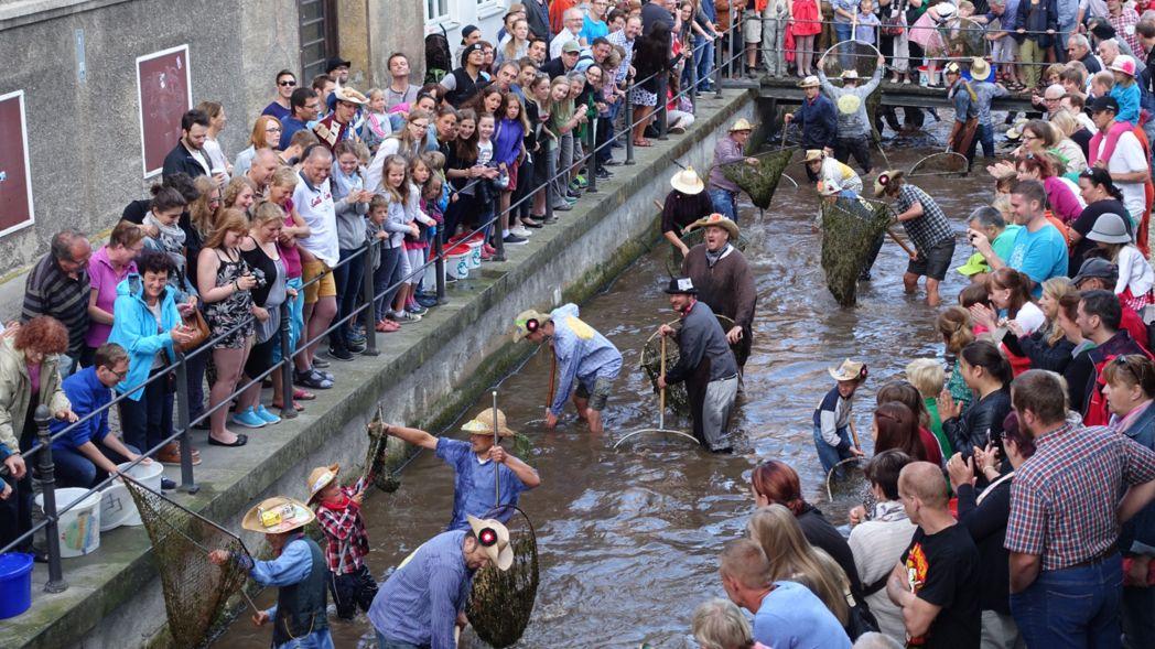 Historisch gewandete Memminger fischen beim Fischertag den Stadtbach aus