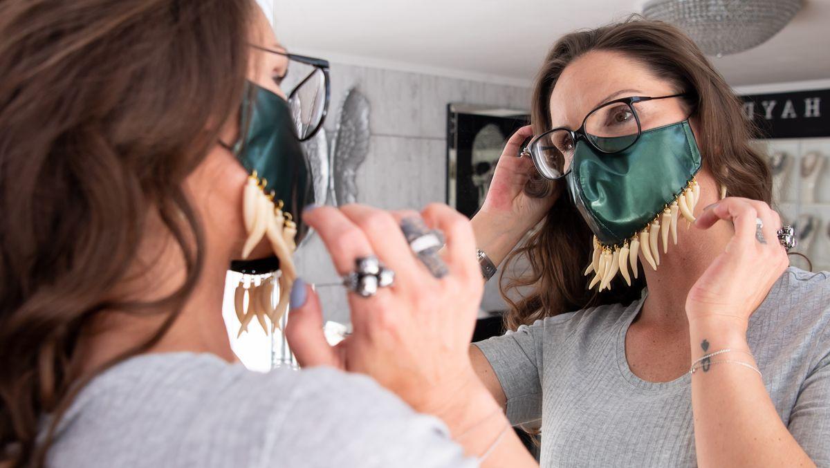 Nicole Hayduga trägt einen Designer-Mundschutz. Er ist grün, am unteren Ende baumeln Plastikzähne.