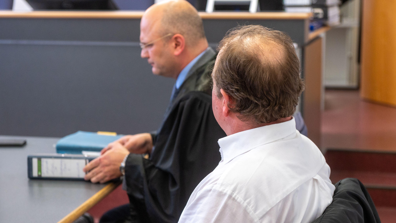 Der Angeklagte (r.) sitzt im Verhandlungssaal des Landgerichts neben seinem Verteidiger.