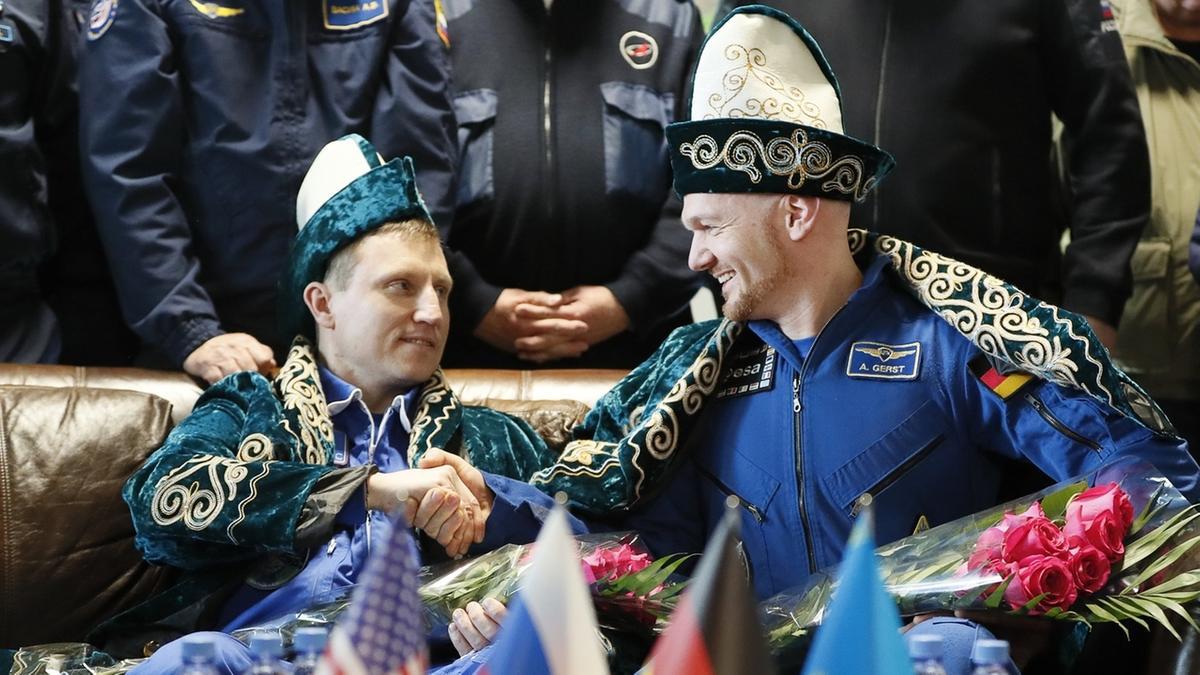 Kosmonaut Sergej Prokopjew (links) aus Russland und Astronaut Alexander Gerst aus Deutschland in kasachischer Tracht während einer Pressekonferenz am Flughafen in Scheskasgan, Kasachstan. Kurz zuvor waren die beiden zusammen mit ihrer US-amerikanischen Kollegin Serena Auñón-Chancellor an Bord einer Sojus-Raumkapsel auf der Erde gelandet, nachdem sie über ein halbes Jahr auf der Internationalen Raumstation ISS verbracht hatten.