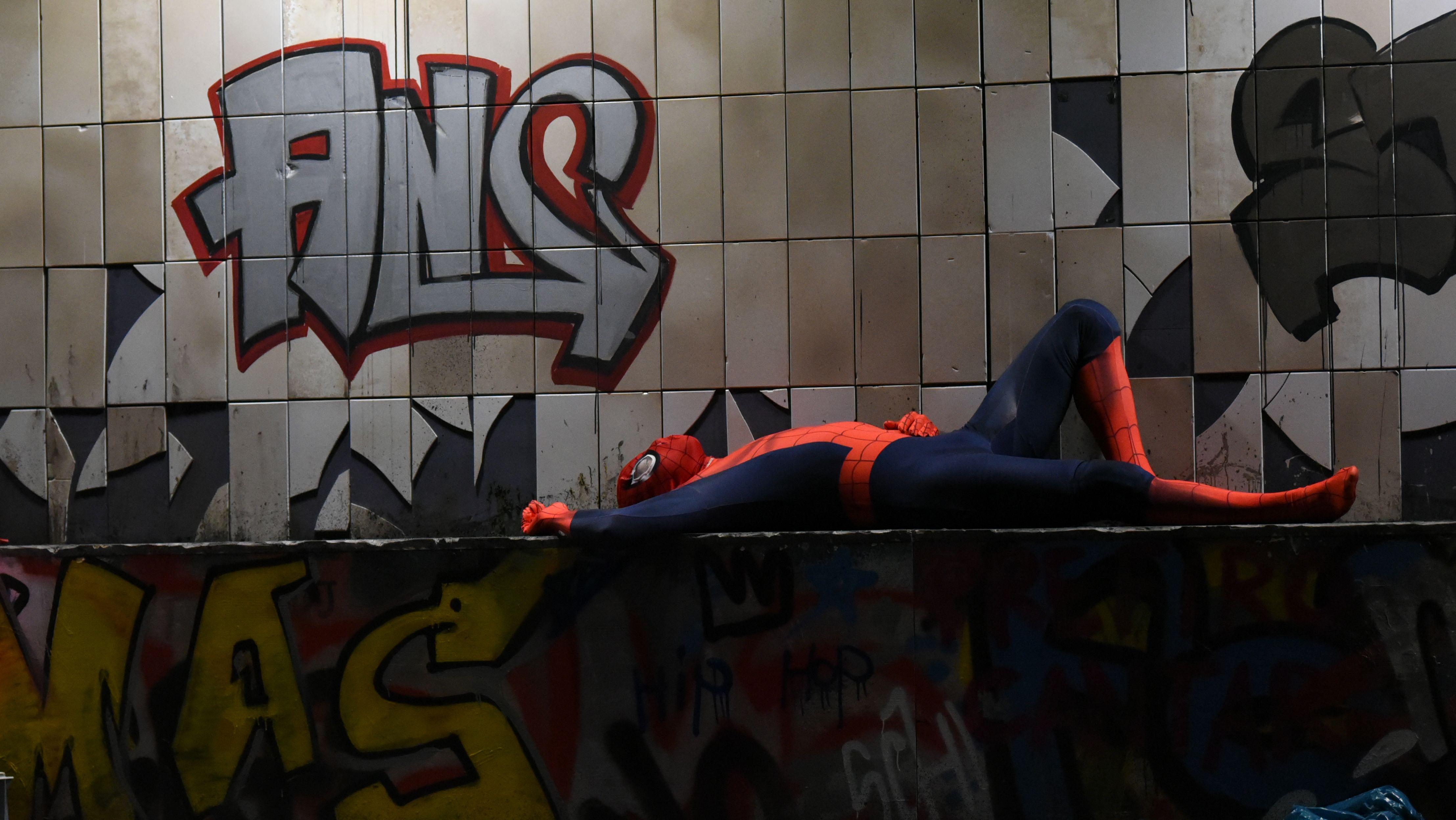 Don Quichotte liegt in einem Spiderman-Kostüm vor einem Graffiti und träumt