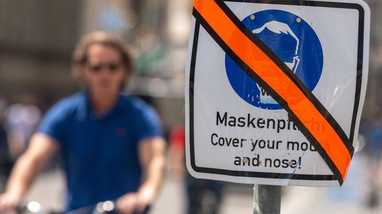 Ein mit orangen Klebeband durchgestrichenes Schild mit der Aufschrift «Maskenpflicht - Cover your mouth and nose!» steht in der Innenstadt am Straßenrand. | Bild:picture alliance/dpa | Peter Kneffel