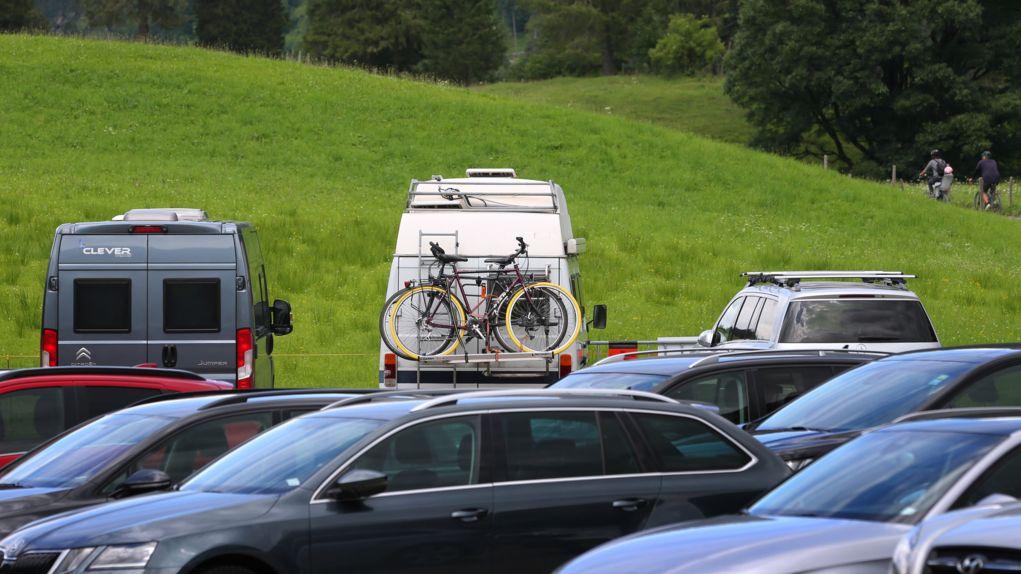 Parkplatz mit PKW und Campingbussen mit Fahrrädern vor grüner Wiese