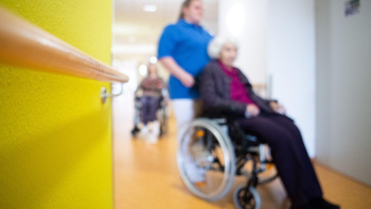 Eine Pflegerin schiebt eine Bewohnerin eines Pflegeheims in einem Rollstuhl über den Flur