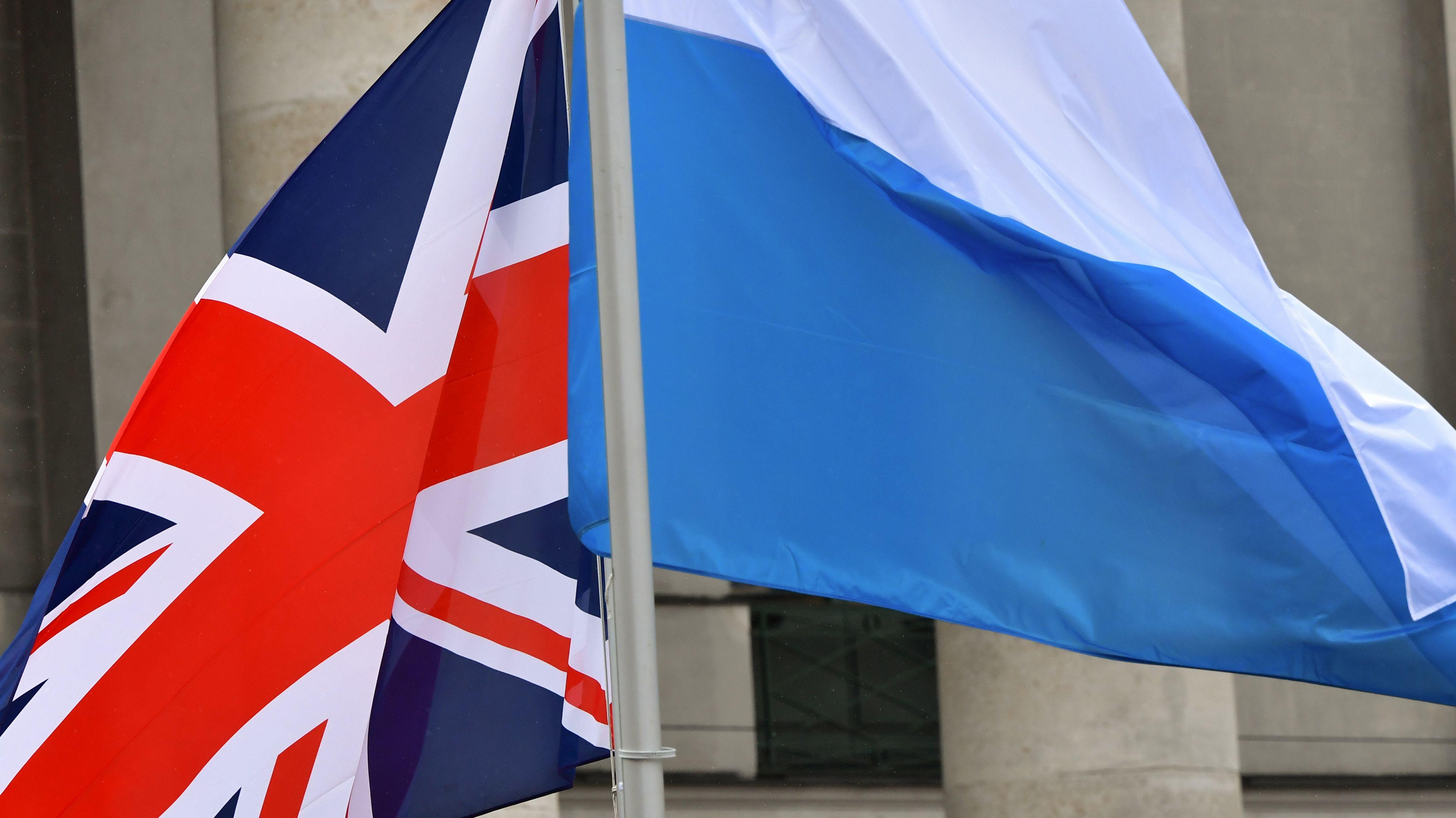 Eine britische und eine bayerische Flagge wehen nebeneinander.
