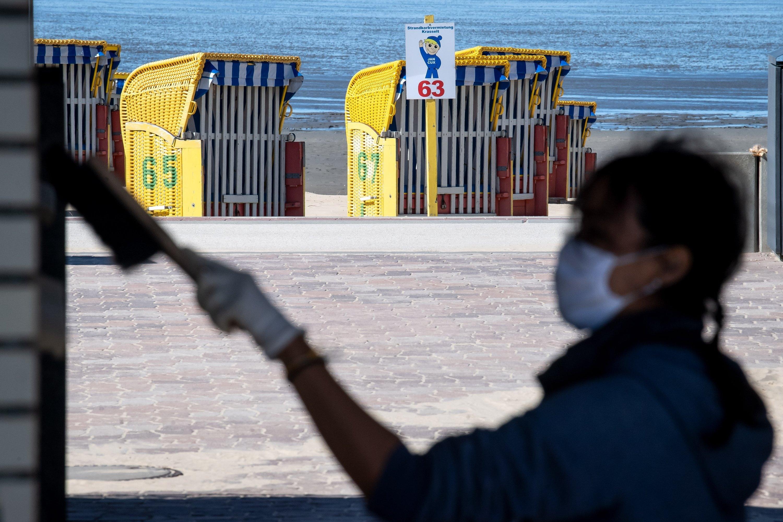Eine Frau mit Schutzmaske bürstet die Fassade eines Gebäudes an der Küste vor Strandkörben ab.