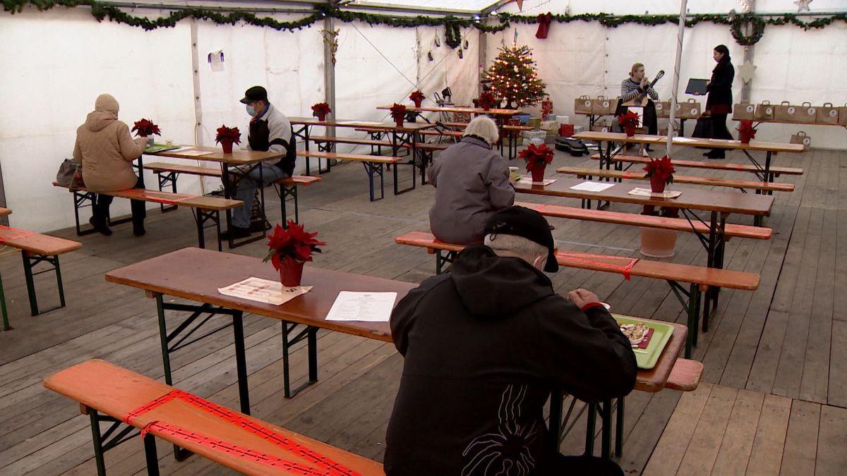 Ein größeres, weihnachtlich geschmücktes Zelt in Augsburg, in dem einige Bedürftige sitzen.